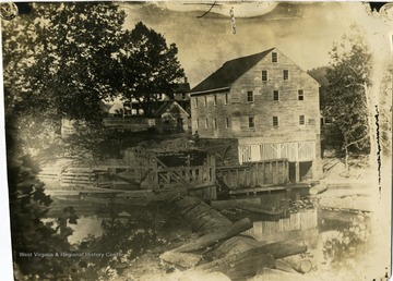 A view of Jackson's Mill with a man beside the building. 'Photo by or for Sam Barret.'