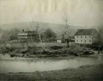 A view of Jackson's Mill, some buildings to the left of the mill, and the river.
