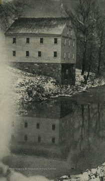 A view of the mill in the winter, with snow along the riverbanks.