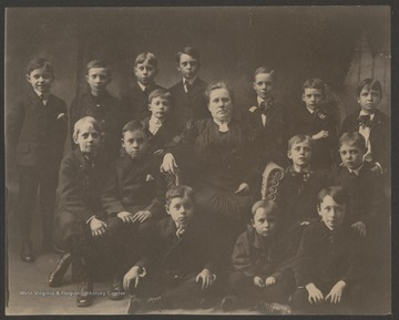 In the front row, from left to right, is Terrence Moorefield, Fred Brown, and Boyd Brown.In the second row, from left to right, is Christian Hetzel, George Griffith, Clemmer Peck, Mrs. Carrie B. Mahon (teacher), Reese Capeller, and Stanely Butler.In the back row, from left to right, is William Moorefield, Cecil Hinton, Julian Fredeking, Roy Mann, Oswald Blackwilder, Leo Ross, and Fred Flanagan.