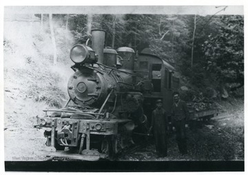 Two men standing to the right of a log engine. Albert Hertig of Evenwood, W. Va. standing on far right.