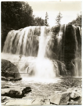There is a woman on a diving board beside the falls.  'Photograph by courtesy of United States Forest Service.'