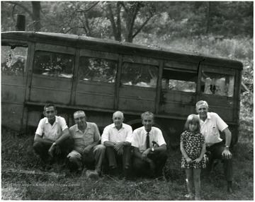 Five men and a young girl in front of the bus.