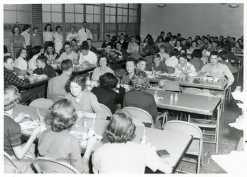 """Alumns serving Rampfeast, 1956, to buy cafeteria equipment.  Sale was a success.  Standing by the wall, left to right, are girls who served food.  Barbara Cogar, Connie Ware, Frances Gladwell, Maxine House.  Cooks who prepared food are Lafa Hosey, Mrs. Olive Nichols, and Robert G. Andrick who was manager of the cafeteria from 1955 to 1960.  At the center of the room is Miss Aretta Summers and Mrs. Ruth Morton Himes, both reflecting appreciation for the new high school building.  They were teachers of whom the school was proud."""
