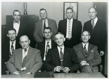 Board of Education and Supervisory Staff, 1956, Webster County, W. Va.  Pictured sitting, left to right; Howard Fletcher, Lawrence Berry, Orvak Cogar, Leslie B. Robinson (president of the board), and Dock Cutlip.  Standing;  Fred Berry (supervisor of instruction), Ed Cunningham (supervisor of transportation, buildings and grounds), John Shock (superintendent of schools), and C. Paul Cutlip (assistant superintendent of schools).