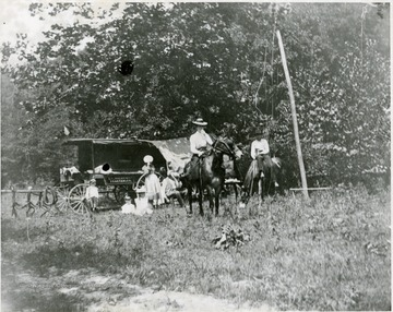 View of Man and lady on horse with children in background.  Sign on buggy reads 'T. A. Haldeman Vegetables'