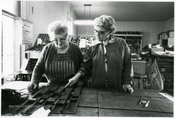 'Making up - Stella McLaughlin and Maxine Dever prepare hand set type for the Marlinton, W. Va. weekly newspaper, The Pocahontas Times.'