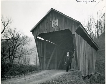 View of man standing at bridge entrance.