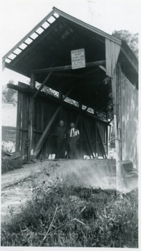 View of two men standing at entrance of bridge.