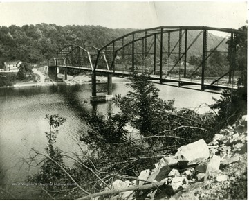'Cheat River Bridge after the other washed away in 1918.  This was not built upon the same piers and was a short distance further north.  The old one went across from bluff to about where the shelving rock goes out (people swim and fish there now).  Toward Mont Chateau.  This same bridge was raised and added to when lake went in in 1926.""