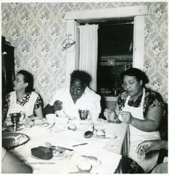 Three African-American women participate in a Make Your Own Mix demonstration.
