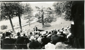 Group seated on a hillside listening to speaker.