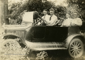 In the driver's seat is Warren Cunningham, beside him is Bradford Cunningham, and in the backseat is Oather Cunningham and Homer Lovejoy.