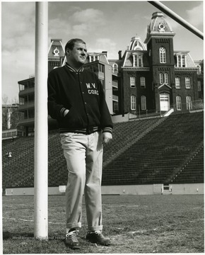 Coach is standing on Mountaineer field below Woodburn Hall.