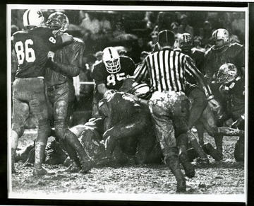 Football players are in a muddy pile up during the 1969 Peach Bowl in Atlanta, Georgia where West Virginia beat the University of South Carolina.