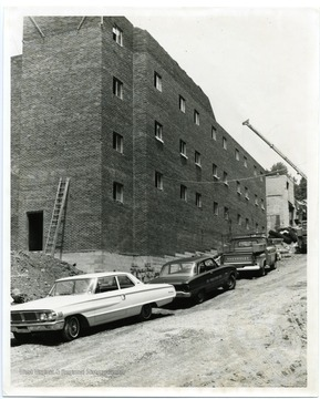 Cars are parked near the construction of Carlisle Hall, West Virginia University.
