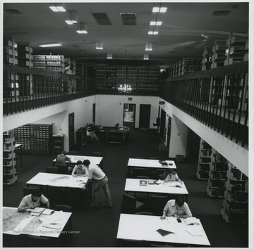 Students researching at tables in the West Virginia Collection. View looking down from the mezzanine.