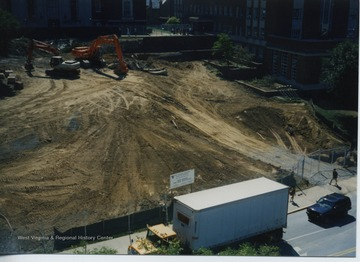 Shows earth moving equipment in place after the lawn was removed but before major excavation in front of Wise Library began.  Front entrance was still open.