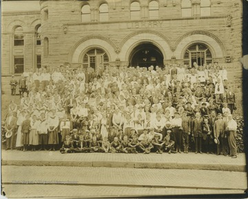 A group of women, men, and children, who are likely members of a 4-H group. The group is in front of the library, which is now Stewart Hall.