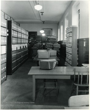 Books and paper in background. Boxes on the shelves on the left. Table and chairs in the foreground.