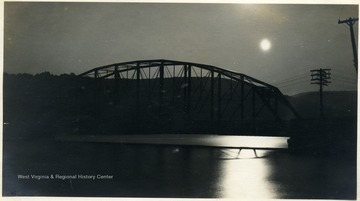 Full moon shining over the Cheat River and bridge.