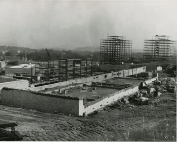 Foreground view of construction of Forestry building.  Background, right, construction of Twin Towers.