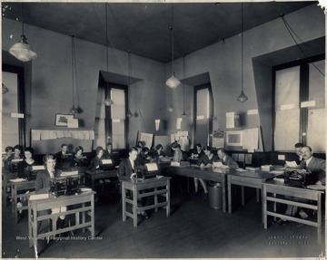 Students sitting at desks and tables using typewriters.
