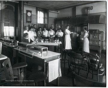 Class members cooking in a kitchen classroom.  'Lady standing at far left:  Miss Rachel Colwell; man in middle back row:  Thomas E. Hodges, President of WVU.'