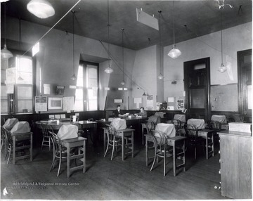 Two men sit at desk in back of room filled with desks and covered typewriters.