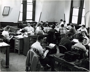 A room full of students working at typewriters in Journalism School.