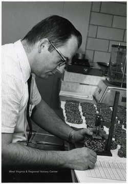 'WVU Researcher Byron Ruth tabulates data from samples taken from various roads throughout the state.  Checking the compaction of each disk, Ruth receives samples from test roads in Wetzel, Monongalia, Berkeley, and Raleigh counties.'