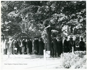 'Commencement participants standing in front of E. Moore Hall'.