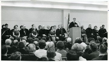 'Dr. Harry Heflin, acting president at podium, and various faculty members' including Dr. Wes Bagby seated at far right, Stillwell seated third from right, and Ruel Foster seated at far left.