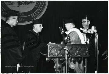 President Paul Miller granting a degree, left; Stan Harris on right.