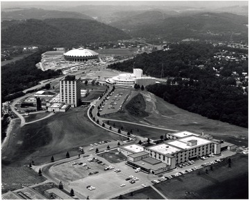 'West Virginia University's Evansdale Campus -- one of the three Morgantown campuses -- sprawls from the banks of the Monongahela River almost to the Medical Center. Buildings shown (from river to foreground) are the Coliseum (under construction,) the Creative Arts Center, the Engineering Sciences Center and the Agricultural Sciences Building.'