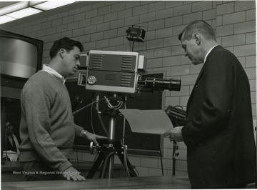 'Dr. Jay Barton, (right) Chairman of the WVU Biology Department, outlines to TV cameraman John Stone of Morgantown, the 50 minute lecture, he will tape for the Biology I course. As soon as it is completed, Barton will have the opportunity to watch a re-play of the lecture and can, if he chooses, change parts of it.'