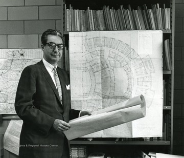 Dean Duncan standing in front of architectural plans for the Creative Arts Center.
