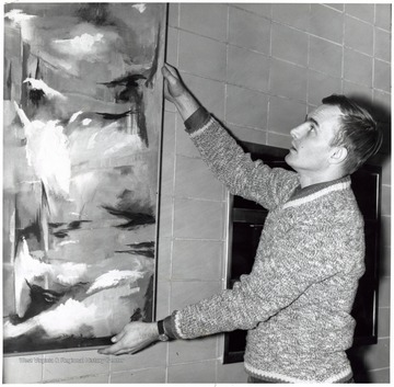 Joe Moss positioning a painting.
