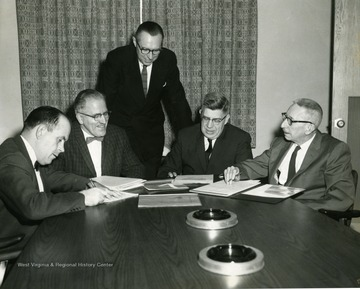 Weaver, far left; Longhouse, Chairman of Engineering, second from left; Chester Arents, Dean of Engineering, standing; Harold B. Fairbanks, Chemical Engineering, second from right; Howard P. Simons, Chemical Engineering, right.