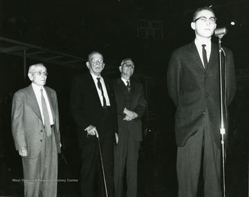 Faculty Day program-half time VMI-WVU Basketball game, February 13, 1959 honoring the three profesor emeriti of West Virginia University. From left, Dr. A. M. Reese, Dr. John B. Grumbein, Dr. Oliver P. Chitwood.