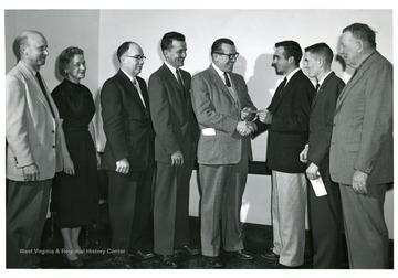 'Left to right: C.P. Dorsey (state 4-H club leader), Mrs. Mary Rose Jones (Assistant Professor of Home Economics, Chairperson Aids and Grants Committee, College of Agriculture Forestry and Home Economics), Dr. A.H. Van Landingham (Acting Dean, College of Agriculture and Forestry and Home Economics), G.W. Melvin (Representative, Esso Standard Oil Company, Morgantown, W.Va.), M.F. Kennedy (Representative, Esso Standard Oil Company, Fairmont, W.Va.), Edwin Townsend (Wood County, Senior, College Agriculture, Forestry, and Home Economics), John Wolfenbarger (Greenbrier County, Freshman, College of Agriculture, Forestry and Home Economics), J.O. Knapp (Director, Agricultural Extension Service, West Virginia University).'