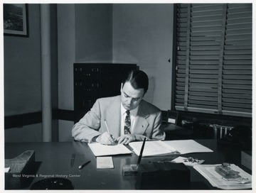 Harry Ross Varney writing at his desk.