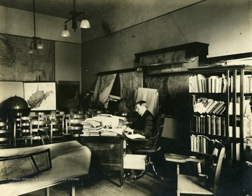 'Unidentified faculty member at his desk surrounded by maps and books. He is probably a member of the faculty of the Geography department, and his office is probably in Woodburn Hall.'