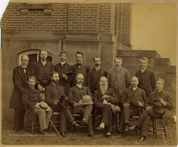 The faculty in the back row, left to right, are named as the following:  John Harvey, Professor of Modern Language; R. C. Berkeley, Professor of Language; James Wilson, Professor of Math and Military; P. B. Reynolds, Professor of English; A. R. Whitehill, Professor of Chemistry; I. C. White, Professor of Geology; and W. P. Willey, Professor of Law.  The faculty in the front row, listed left to right, are named as the following:  St. George Tucker Brooke; D. B. Purinton, Professor of Metaphysics; Pres. E. M. Turner, Professor of Rhetoric; Okey Johnson, Professor of Law; A. Lorentz; and T. S. Stewart, Professor of Mathematics.  The subjects in the photograph were identified by Mr. Bayles and Dr. Callahan.
