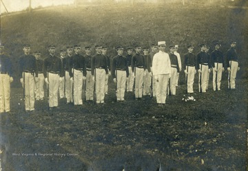 'Drill field at WVU. Ellison in all white uniform'.