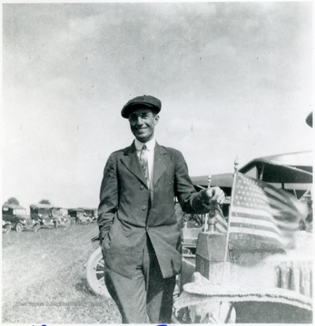 George Green standing beside a car with American flags.
