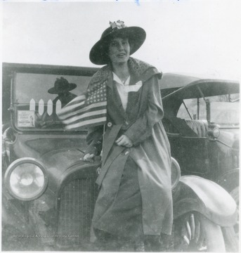Bernice Green leaning against a four cylinder Dodge car.