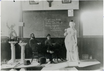 On the chalkboard is written, 'Leach and Davis, Seniors.  Venus and Mercury Guardian Angels, February 12, 1898.'
