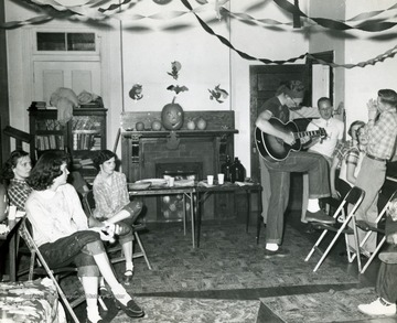 Man with a guitar entertains the group.