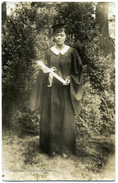 Portrait of African-American student, Stella Boyd, in cap and gown holding her diploma upon graduation from Storer College.